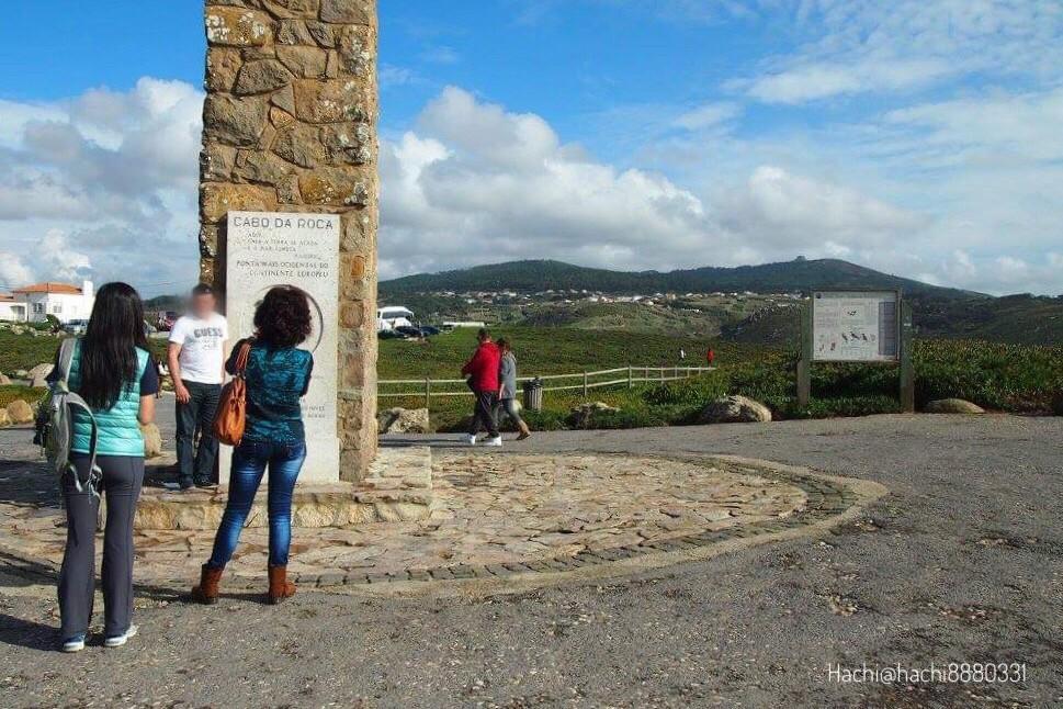 ロカ岬のここに地終わり海始まる(Onde a terra se acaba e o mar começa)が刻まれた石碑の前で記念撮影をする観光客